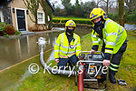 Killarney firemen Jonathan O'Connor right and Paul Sheehan pumping out water from a flooded house yard in Fossa on Tuesday morning