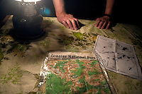 A trail map for the Many Glacier area (right) and a topographical map printed on a bandana lay on a picnic table of a campsite at the Many Glacier campground in Glacier National Park in Montana.