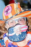 """Terry Johnson, 67, of North Conway, NH, wears American flag- and Trump-themed campaign buttons, facemask, glasses, and hat, after hearing Donald Trump, Jr., son of president Donald Trump and a rising Republican political star, speak at an outdoor campaign rally at The Lobster Trap in North Conway, New Hampshire, on Thu., Sept. 24, 2020. Johnson said that the president had signed her """"Hot chicks for Trump"""" button and her hat at earlier rallies."""