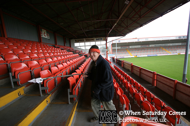 A member of the groundstaff picking up litter at Morecambe Football Club's Christie Park. The club was preparing for the club's first-ever season in the Football League having been promoted from the Conference the previous season.  Photo by Colin McPherson.