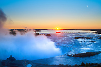 Amazing Niagara Falls horseshoe misty sunrise, with Table Rock Welcome Center in foreground and an orange sun and sky below the moon, Ontario Canada