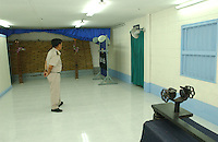 The exection chamber in Thailand's  Bangkwang Central Prison.  The  condemmed men are strapped to the wooden execution cross at the back of the room. a machine gun is mounted on the metal frame in the fore-ground.