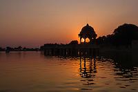 Stone tower in sacred Gadi Sagar lake in Jaisalmer, India during sunset