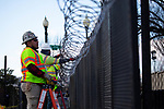 Workers install barbed wire on fencing in front of the U.S. Capitol ahead of President-Elect Joe Biden's Inauguration on January 19, 2021 in Washington, D.C..  Photograph by Michael Nagle