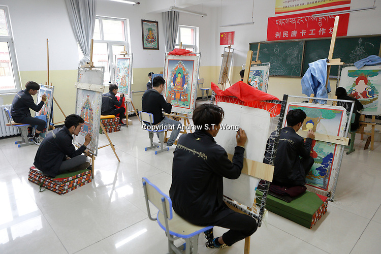 Yushu City, Yushu Tibetan Autonomous Prefecture, Qinghai Province, China - Tibetan youths learn how to draw Thangka, a Tibetan Buddhist painting on cotton, silk appliqué, usually depicting a Buddhist deity, scene, or mandala, August 2019.