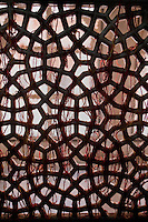 Fatehpur Sikri, Uttar Pradesh, India.  Geometric Pattern in  Window Lattice-work of the Mausoleum of Sheikh Salim Chishti.  Visitors tie red thread as a symbol of prayers offered, usually in hopes of conceiving a child.