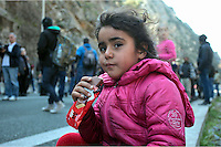 Pictured: A young girl sits on the hard shoulder to have some chocolate Thursday 25 February 2016<br />Re: Hundreds of migrants, including families with young children, that were stranded at Tempe in central Greece, were forced to walk on foot on the motorway to reach Idomen, about 168 kilometres away, in the northern part of the country, at the Greek FYRO Macedonian border. Local police were at first escorting them, then made sure that they were safely transported on coaches.