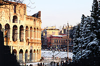 Rome, Fora:  A peculiar view of the back side (with respect to via dei Fori) of the Colosseum and of its surroundings, in the late afternoon, after a snowing night (February, 2012). There are quite a lot of people, too. One can see in particular a slope traced by persons that used it to slide, and trees almost completely covered by snow. This is an enlargement of a part of the original photo.<br /> <br /> This photo is available as  Editorial only.