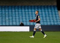 31st October 2020; The Den, Bermondsey, London, England; English Championship Football, Millwall Football Club versus Huddersfield Town; Shaun Hutchinson of Millwall walks onto the pitch holding a poppy wreath