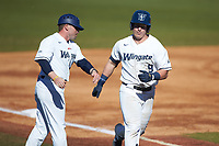 McCann Mellett (9) of the Wingate Bulldogs is congratulated by third base coach Jacob Rand after hitting a home run against the Concord Mountain Lions at Ron Christopher Stadium on February 2, 2020 in Wingate, North Carolina. The Mountain Lions defeated the Bulldogs 12-11. (Brian Westerholt/Four Seam Images)