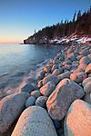 A golden winter sunrise illuminates the oversized boulders at Boulder Beach in Acadia National Park, Mount Desert Island, Maine, USA