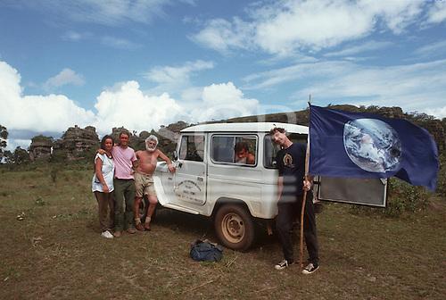 Chapada dos Guimaraes, Mato Grosso, Brazil. Ed Posey, Liz Hosken, Mario Friedlander, Jorge and Patrick Cunningham with the Gaia flag; 1990.