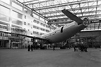 Usine de l'Aérospatiale de Saint-Martin-du-Touch, grand hall de montage. 5 février 1972. Vue d'ensemble de l'Airbus A300 B (vue de côté) ; techniciens autour de l'avion. Cliché pris lors du 1er déplacement tracté de l'avion encore en cours de montage.