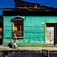 A Salvadoran man walks in front of a common lower middle class house, designed by using bold Spanish colonial architecture elements, built in a working class neighborhood of San Salvador, El Salvador, 14 November 2016.