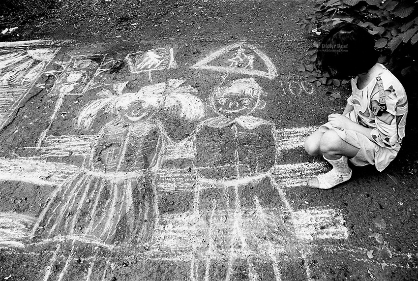 "Kazakhstan. Semipalatinsk. The first of june is ""Children Defense Day"". A girl with a white chalk sketches a couple of happy children and traffic lights on the ground of the park. Semipalatinsk has lived in the shadow of the Soviet atomic test program 456 atomic testing - 116 atmospheric, 340 underground - from 1949 to 1989 at Semipalatinsk Polygon ( called today National Nuclear Center of Kazakhstan). The regions of Semipalatinsk has a high frequency of various diseases primarily due to fallout from nearby nuclear test sites, as human and environmental effects of nuclear radiation, contamination and pollution from atomic tests programs of the former Soviet Union. Semey is the Kazakh name for Semipalatinsk and is located in the Eastern Kazakhstan Province. © 2008 Didier Ruef ."