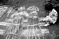 """Kazakhstan. Semipalatinsk. The first of june is """"Children Defense Day"""". A girl with a white chalk sketches a couple of happy children and traffic lights on the ground of the park. Semipalatinsk has lived in the shadow of the Soviet atomic test program 456 atomic testing - 116 atmospheric, 340 underground - from 1949 to 1989 at Semipalatinsk Polygon ( called today National Nuclear Center of Kazakhstan). The regions of Semipalatinsk has a high frequency of various diseases primarily due to fallout from nearby nuclear test sites, as human and environmental effects of nuclear radiation, contamination and pollution from atomic tests programs of the former Soviet Union. Semey is the Kazakh name for Semipalatinsk and is located in the Eastern Kazakhstan Province. © 2008 Didier Ruef ."""