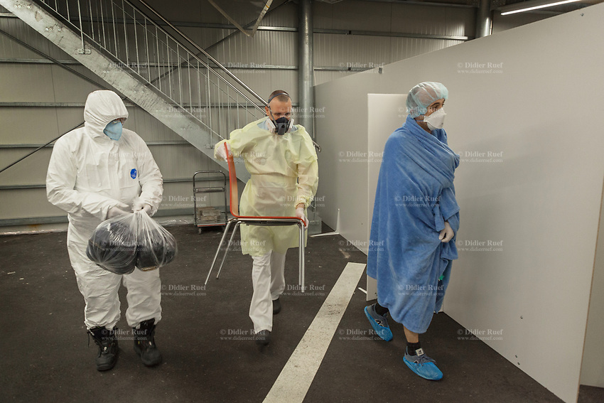 Switzerland. Canton Ticino. Lugano. Due to the spread of the coronavirus (also called Covid-19) and given the increase in cases in Ticino, the Clinica Luganese Moncucco was transformed into a Covid-19 Hospital. Hospital's entrance. Sorting patients. A nurse dressed in hazmat suit stands close to a man seated on a chair. The young man is a suspected coronavirus patient. The nurse is dressed in protective clothing that seal her off the contaminated environment. He wears FFP2 masks, latex medical gloves, protective glasses and clothing. All men wear single-use mask protecting against solid and liquid particles. The Safemask Premimum offers respiratory protection to medical staff. Medical gloves are disposable gloves used during medical examinations and procedures to help prevent cross-contamination between caregivers and patients. In the fight against the coronavirus, nurses play a critical role, but some on the front lines in the hardest-hit areas fear for their health. 25.03.2020 © 2020 Didier Ruef