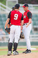 Kannapolis Intimidators pitching coach Larry Owens #14 (right) chats with pitcher Ryan Buch #9 and catcher Miguel Gonzalez #12 during a South Atlantic League game against the Hickory Crawdads at Fieldcrest Cannon Stadium August 18, 2010, in Kannapolis, North Carolina.  Photo by Brian Westerholt / Four Seam Images