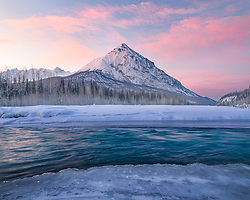 King's peak framed with a colorful sunrise and glacial runoff in Alaska's Chugach Range.