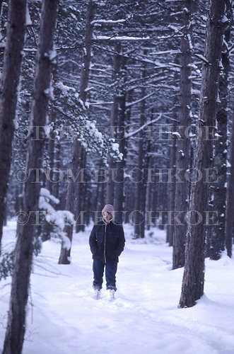 Young woman walking in the winter  woods in the Upper Peninsula of Michigan.