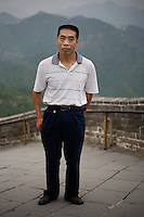 Zhangkaiming, a public servant, age 49, poses for a portrait in Badaling. Response to 'What does China mean to you?': 'China is lovingly peaceful and lovingly friendly.'  Response to 'What is China's role in the future?': 'China will definitely make use of its position on the international platform'