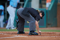 Home plate umpire Jennifer Pawol cleans home plate during the South Atlantic League game between the Hickory Crawdads and the Ocelotes de Greensboro at First National Bank Field on June 11, 2019 in Greensboro, North Carolina. The Crawdads defeated the Ocelotes 2-1. (Brian Westerholt/Four Seam Images)