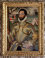 One of the 16th century portraits of a man in armour hangs in an ornate carved and gilded frame in the dining room