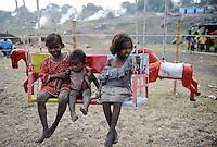 INDIA Jharkhand Dhanbad Jharia , children in carousel , background smoke of burning underground coal seams, children work as coal picker / INDIEN Kohlerevier Dhanbad / Jharia , Kinder im Karussell auf einem Jahrmarkt vor brennenden Kohlefloezen, Kinder sammeln Kohle in Abraumhalden um Geld fuer die Familie zu verdienen