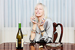 Senior Woman with gawdy jewels sitting at table with wine.
