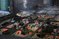 Bali, Indonesia.  Grilling Fish over a Charcoal Fire at a Small Fast Food Stand in the Jimbaran Fish Market.