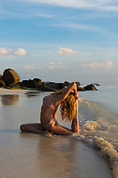 Thai beach yoga - girl in pigeon pose on Ko Lipe island, Thailand