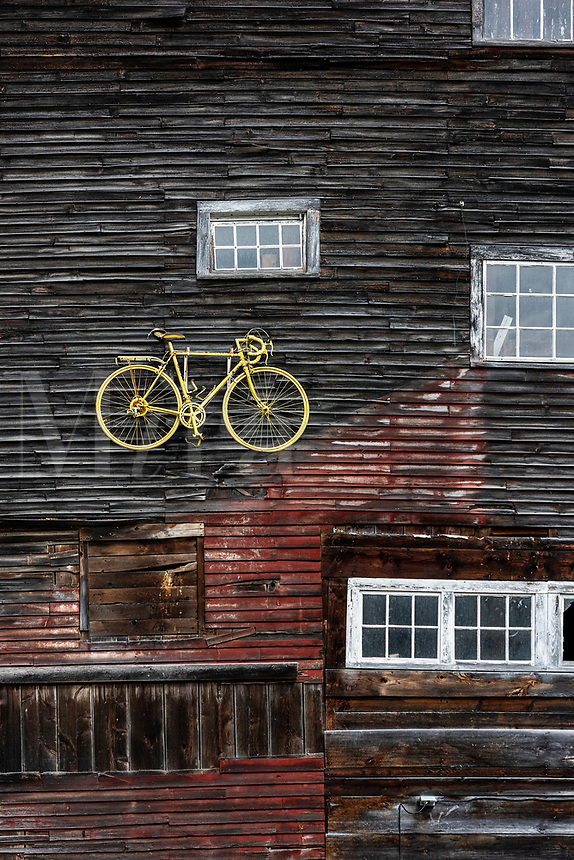 Yellow bike displayed on a barn  exterior facade, Vermont, USA.