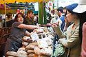London, UK. 25.10.2014. Female stallholder selling bread at Borough Market, Southwark. Photograph © Jane Hobson.