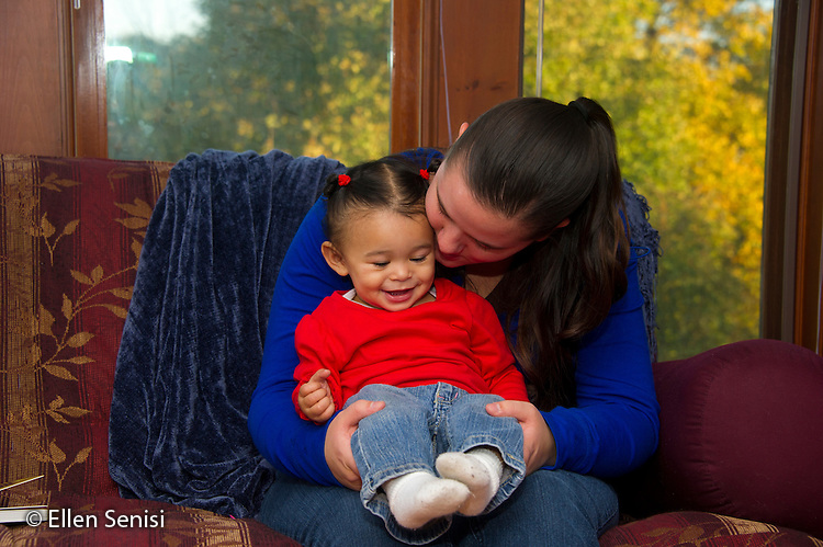 MR / Schenectady, NY. Mother (21) holds her infant daughter (11 months, African American & Caucasian) and whispers in her ear. MR: Dal4, Dal6. ID: AL-HD. © Ellen B. Senisi