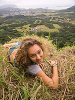 A young local woman rests near the Pali Lookout, with Windward O'ahu in the distance.
