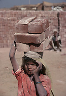 Child is working at brick manufactuer in India - Child labor as seen around the world between 1979 and 1980 - Photographer Jean Pierre Laffont, touched by the suffering of child workers, chronicled their plight in 12 countries over the course of one year.  Laffont was awarded The World Press Award and Madeline Ross Award among many others for his work.