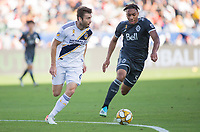CARSON, CA - SEPTEMBER 29: Dave Romney #4 of the Los Angeles Galaxy moves with the ball past Theo Bair #50 of the Vancouver Whitecaps during a game between Vancouver Whitecaps and Los Angeles Galaxy at Dignity Health Sports Park on September 29, 2019 in Carson, California.