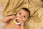 Infant boy age 6 months on back closeup holding and mouthing toy rattle