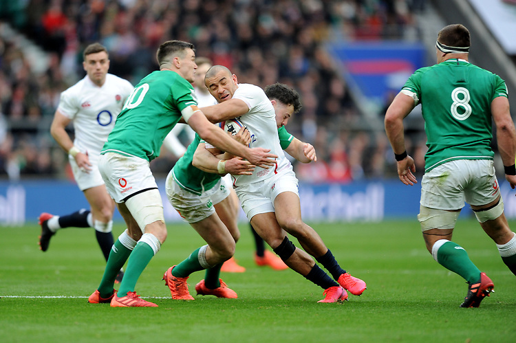 Jonathan Joseph of England is tackled by Robbie Henshaw and Jonathan Sexton (c) of Ireland during the Guinness Six Nations match between England and Ireland at Twickenham Stadium on Sunday 23rd February 2020 (Photo by Rob Munro/Stewart Communications)