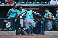 Blaine Crim (9) of the Llamas de Hickory has water thrown in his face as he returns to the dugout after hitting a home run against the Winston-Salem Rayados at Truist Stadium on July 6, 2021 in Winston-Salem, North Carolina. (Brian Westerholt/Four Seam Images)