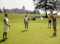Women putting on the golf green in front of the hotel.