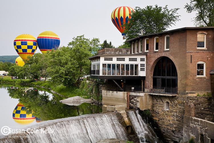 Hot air balloons float above the Ottaquechee River Dam at the Quechee Balloon Fest in Quechee, VT, USA
