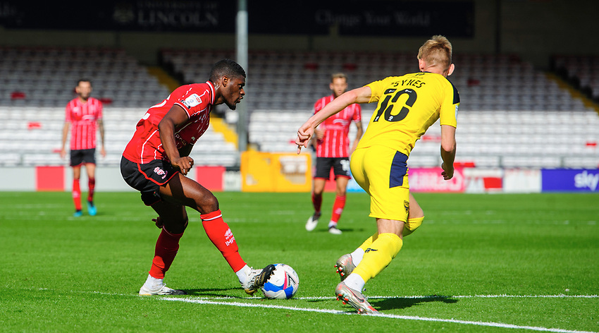 Lincoln City's Timothy Eyoma vies for possession with Oxford United's Mark Sykes<br /> <br /> Photographer Chris Vaughan/CameraSport<br /> <br /> The EFL Sky Bet League One - Saturday 12th September 2020 - Lincoln City v Oxford United - LNER Stadium - Lincoln<br /> <br /> World Copyright © 2020 CameraSport. All rights reserved. 43 Linden Ave. Countesthorpe. Leicester. England. LE8 5PG - Tel: +44 (0) 116 277 4147 - admin@camerasport.com - www.camerasport.com - Lincoln City v Oxford United