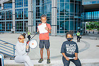 """Rally organizer Naheem Benalfew, 7, (standing) speaks to the crowd about equality and fear for black lives outside the Boston Police Department Headquarters during the """"Peaceful Children's March: Be the Change"""" demonstration in support of Black Lives Matter in Boston, Massachusetts, on Sun., June 7, 2020. Jay'dha Rackard, 11, (left) holds the bullhorn while Benalfew speaks and sister Anaysha Benalfew, 10, who also helped organize the rally, looks on. The children's march was organized by siblings Naheem, 7, and Anaysha Benalfew, 10. The demonstration is part of a weeks-long nationwide response to the killing of George Floyd by Minneapolis police on May 25, 2020. The march started near the Nubian Square bus depot and continued to the nearby Boston Police Department headquarters, where marchers knelt for 8 minutes and 46 seconds, the time that police officers knelt on George Floyd's neck during his killing. A number of children, mostly people of color, then spoke about how people should be treated equally and how they wished they didn't have to grow up fearful that a police officer would kill them or their loved ones."""