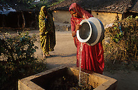 jbo11515 Asia India development climate renewable Energy power decentralized  renewables agriculture gobergas biogas plant for cooking in a village to replace firewoods woman put biomass cow dung and water.Asien Indien Dorf erneuerbare Energie nachhaltigkeit entwicklung Frau gibt Biomasse Kuhdung in Biogasanlage zum Kochen Biogas anstatt Feuerholz.copyright Joerg Boethling / agenda