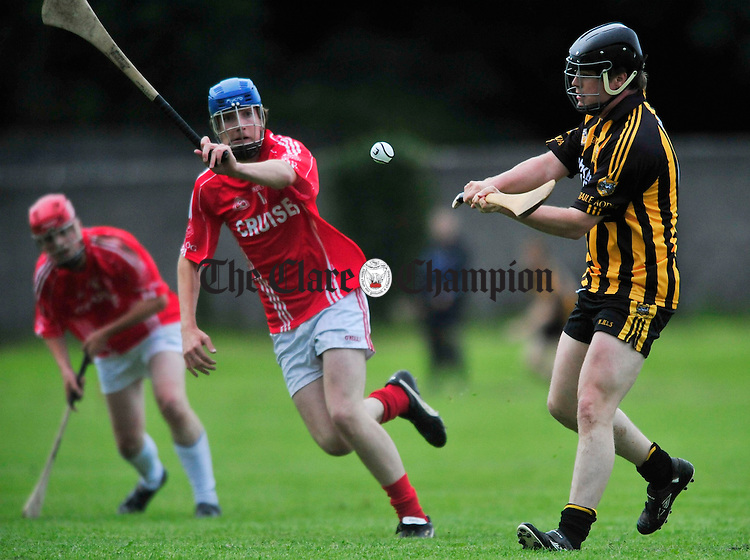 Ballyea's Cyril Carigg passes under pressure from Danny Mc Mahon of Eire Og. Photograph by Declan Monaghan