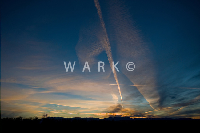 contrails in winter sky at sunset