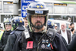 """© Joel Goodman - 07973 332324 . 11/06/2017 . Manchester , UK . A policeman is struck by an egg thrown from the crowd . Demonstration against Islamic hate , organised by former EDL leader Tommy Robinson's """" UK Against Hate """" and opposed by a counter demonstration of anti-fascist groups . UK Against Hate say their silent march from Piccadilly Train Station to a rally in Piccadilly Gardens in central Manchester is in response to a terrorist attack at an Ariana Grande concert in Manchester , and is on the anniversary of the gun massacre at the Pulse nightclub in Orlando . Photo credit : Joel Goodman"""