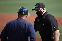 Home plate umpire Brandon Henson explains a call to Old Dominion Monarchs head coach Chris Finwood (5) during the game against the Charlotte 49ers at Hayes Stadium on April 23, 2021 in Charlotte, North Carolina. (Brian Westerholt/Four Seam Images)