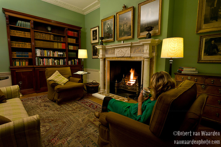 A woman enjoying a cup of tea in the sitting room of the regency country house Cavendish Hall, in Cavendish, Suffolk, United Kingdom. Cavendish Hall is a building belonging to the Landmark Trust, a United Kingdom building preservation charity that rescues historic buildings at risk and gives them a new life as places to stay in and experience.